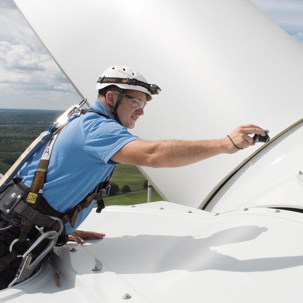 Techniker UKB Rotor Rotorblatt WEA Mann mit Helm Landschaft Wolken Windenergieanlage